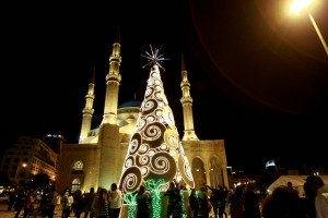 Lebanese people gather around a Christmas tree decorated at Martyrs' Square near the Mohammed al-Amin mosque in downtown Beirut on December 23, 2012. AFP PHOTO/ANWAR AMRO