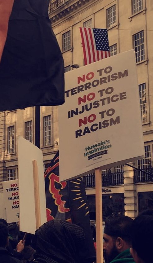 Placards against terrorism, injustice and racism being used by the mourners.